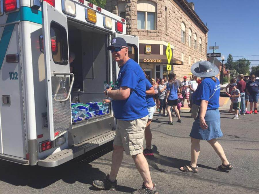 people handing out waters from the back of an ambulance in the parade