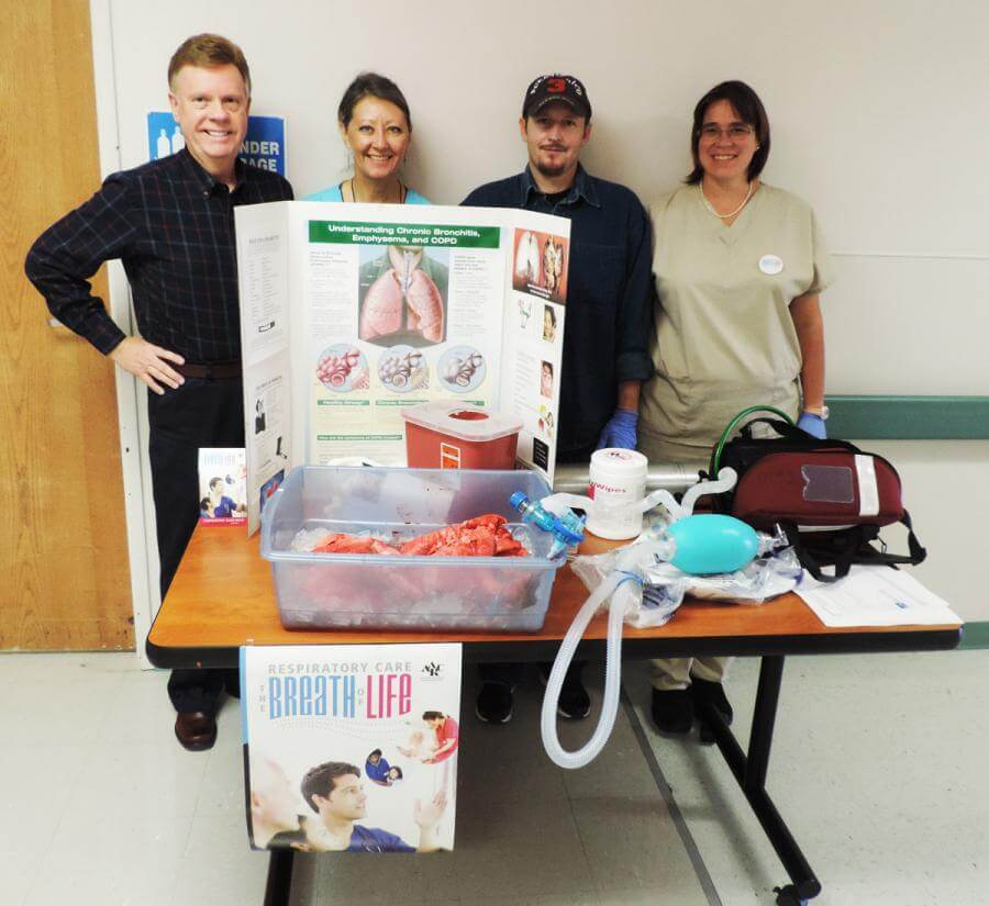 Director of Cardiopulmonary Services Sheridan Moosman (left) and SLV Health's team of Respiratory Therapists stand by the display they created for National Respiratory Care Week.